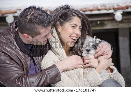 Portrait of a young love couple hugging their dog  in the winter mountain