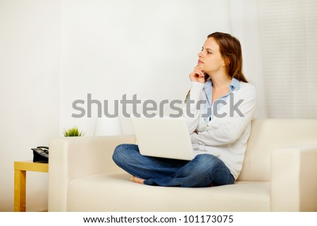 Portrait of a young lovely female thinking on sofa and holding a laptop while resting