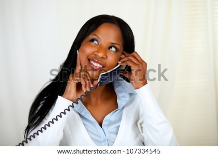 Portrait of a young lovely woman thinking and conversing on phone while looking up - stock photo