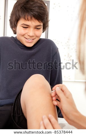 Portrait of a young male acupuncture patient receiving shonishin treatement, shallow depth of field, focus on eyes. - stock photo