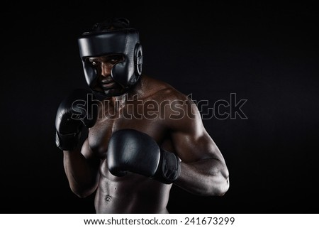 Portrait of a young male boxer in a fighting stance against black background. African young man in boxing gear ready to fight. - stock photo