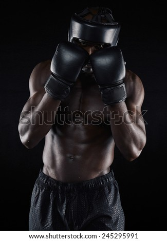 Portrait of a young male boxer in a fighting stance on black background. African male boxer blocking his face with gloves. Young man doing boxing exercise. - stock photo