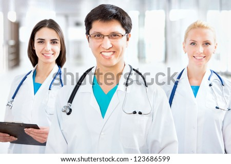 Portrait of a young male doctor standing in front of his team and smiling