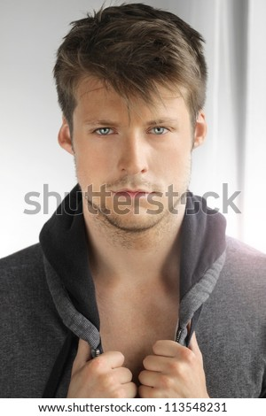 Portrait of a young male model with great face and hands on his jacket - stock photo
