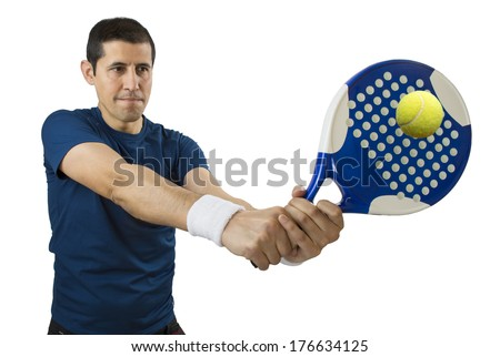portrait of a young male paddle tennis player standing and swatting the ball - stock photo