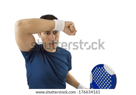 portrait of a young male paddle tennis player standing and wiping sweat after losing service - stock photo