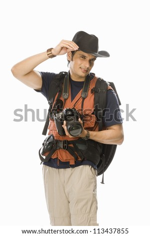 Portrait of a young male photographer holding a digital camera