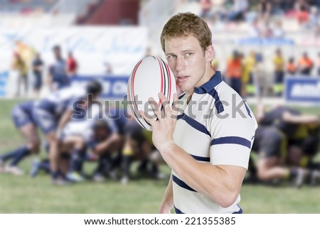 portrait of a young male rugby player standing holding a rugby ball in his hand on a background of a move by rugby - stock photo