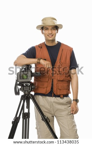 Portrait of a young male videographer holding a videography camera - stock photo