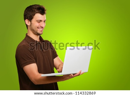 Portrait Of A Young Male With Laptop On Green Background