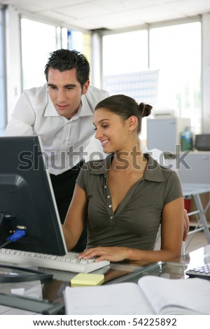 Portrait of a young man and a young woman in front of a laptop computer