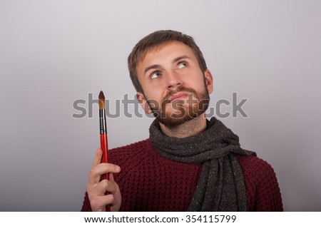 Portrait of a young man artist is holding a brush and thinking - stock photo