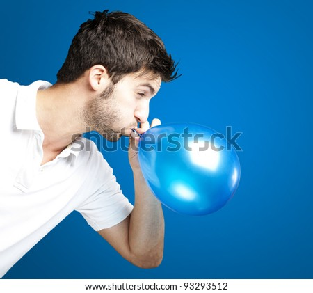 portrait of a young man blowing a balloon over a blue background - stock photo