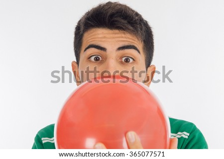 portrait of a young man blowing up a red balloon against a white - stock photo