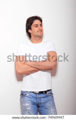 portrait of a young man blue jeans and white tshirt  over light wall - stock photo