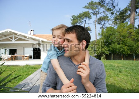 Portrait of a young man carrying a little boy on his back in front of a house - stock photo