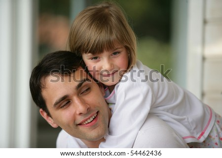 Portrait of a young man carrying a little girl on his back - stock photo