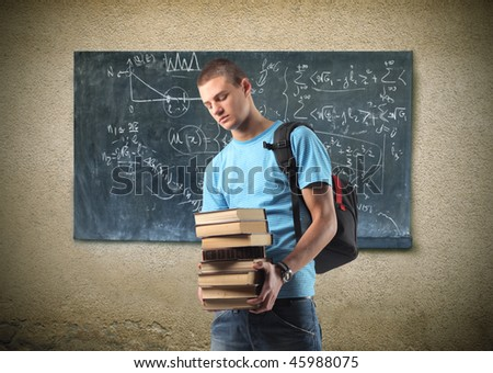 Portrait of a young man carrying some books in front of a blackboard - stock photo
