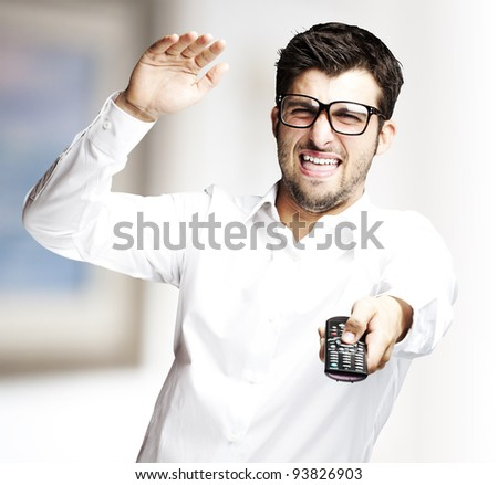 portrait of a young man changing channel with a remote control against an abstract background - stock photo