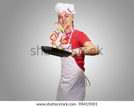 portrait of a young man cooking vegetables with a pan against a grey background