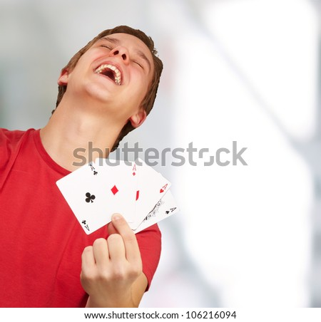 portrait of a young man doing a winner gesture playing poker indoor