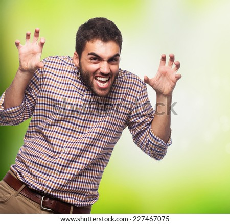 portrait of a young man doing an aggressive gesture with his hands - stock photo
