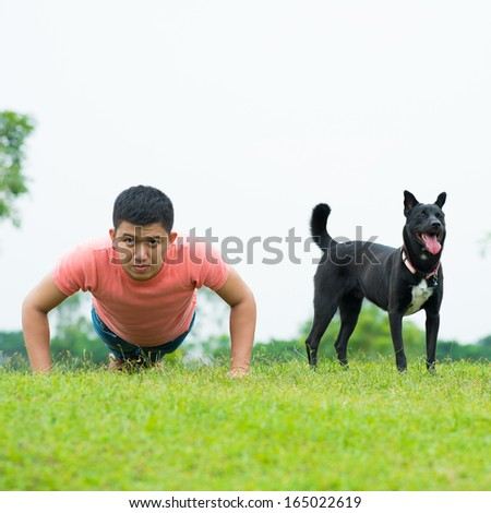 Portrait of a young man doing push-ups with his friend-dog in the park - stock photo