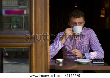 Portrait of a young man drinking coffee and smoking. - stock photo