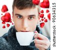 Portrait of a young man drinking coffee while sitting on armchair at home and dreaming about his couple - Indoor. Red hearts are flying around his head. Valentine concept. - stock photo