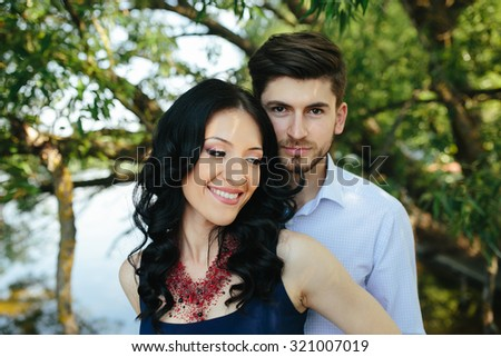 portrait of a young man embracing his girlfriend from behind - stock photo