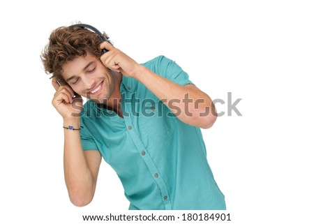 Portrait of a young man enjoying music over white background - stock photo