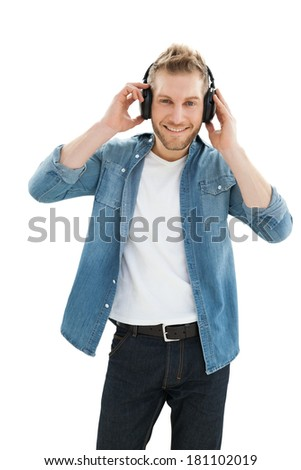 Portrait of a young man enjoying music over white background