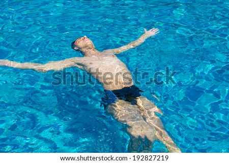 Portrait of a young man floating in the pool. Concept photo healthy lifestyle - stock photo