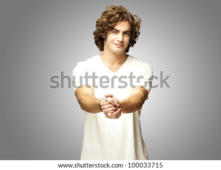 portrait of a young man gesturing a contract over a grey background - stock photo