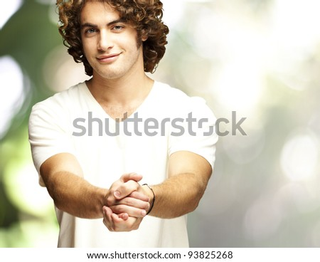 portrait of a young man gesturing contract against an abstract background - stock photo