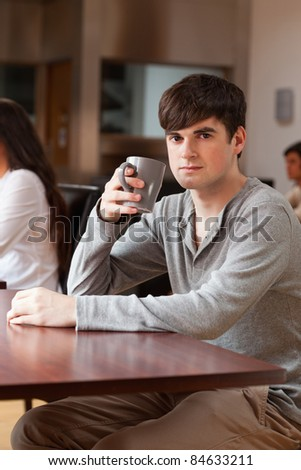 Portrait of a young man having a coffee while looking at the camera - stock photo