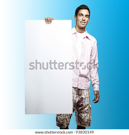 portrait of a young man holding a big white sign against a blue background - stock photo