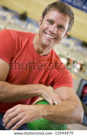 Portrait of a young man holding a bowling ball - stock photo