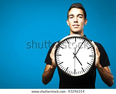 portrait of a young man holding a clock with his hands over a blue background - stock photo