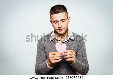 Portrait of a young man holding a large paper heart