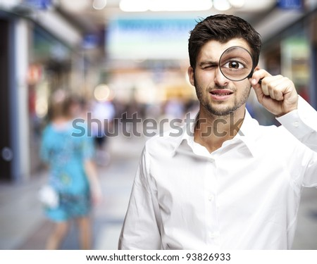 portrait of a young man holding a magnifying glass against a street background - stock photo