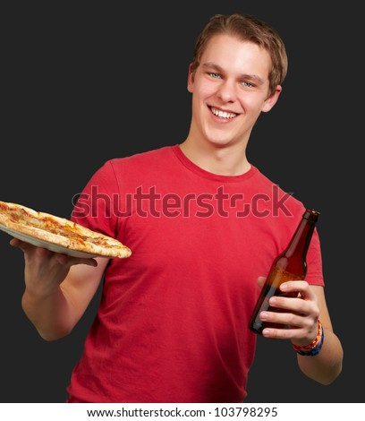 portrait of a young man holding a pizza and a beer over a black background - stock photo