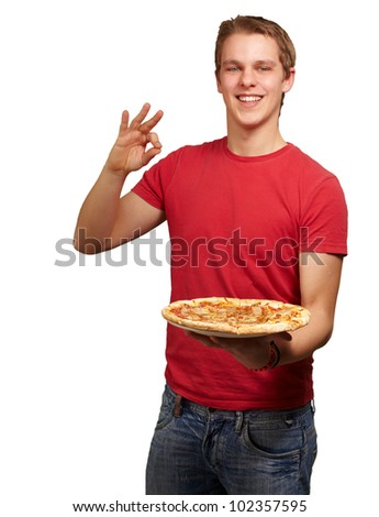 portrait of a young man holding a pizza and doing a good gesture over a white background