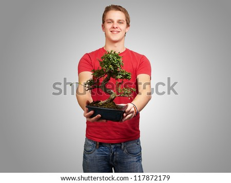 portrait of a young man holding a pot on a grey background