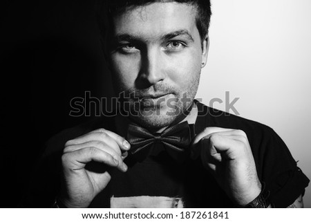 Portrait of a young man in a bow tie with a sly smirk on his face - stock photo