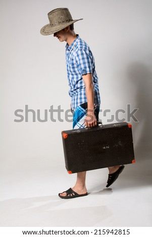 Portrait of a young man in a full-length coming from the suitcase. On a light background in the studio - stock photo