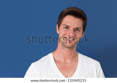 Portrait of a young man in front of a blue background - stock photo
