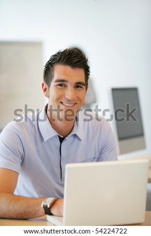Portrait of a young man in front of a laptop computer - stock photo