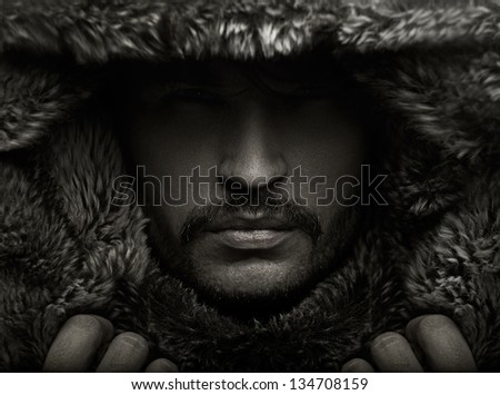 Portrait of a young man in fur hood - stock photo