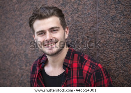 Portrait of a young man in red shirt posing on a stone wall background